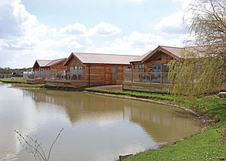 Lakeside setting of lodge at Willow Lakes Holiday Park in Ashby Cum Fenby Lincolnshire