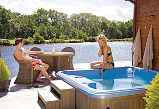 Outdoor hot tub with lake view at The Top Boathouse ( Ref LP6265 ) Anglesey Holiday Lodges in North Wales